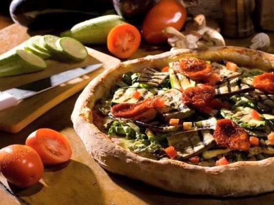 Pizza vegetariana preparada com mozarela de búfala, palmito, champignon, berinjela, abobrinha e toma