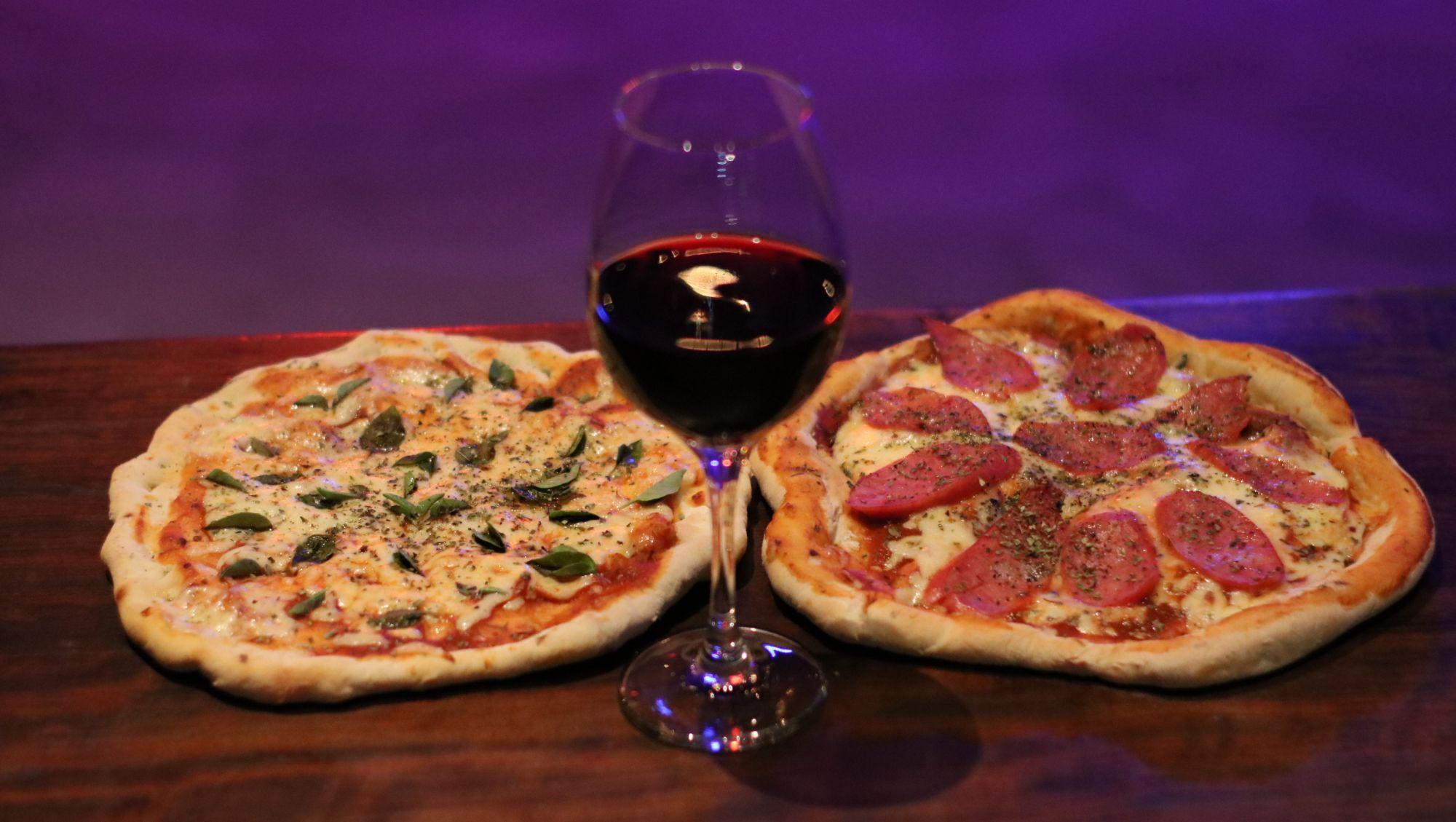 Pizzas do Porta Bar são individuais. Os sabores fixos são margherita (à esquerda) e calabresa. A taça de vinho tinto, não importa o rótulo, sai por R$ 10. Foto: Divulgação