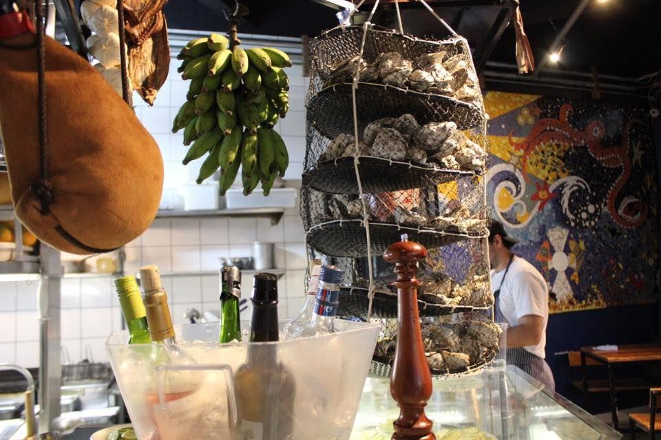 A Ostra Bêbada, no centro de Curitiba, tem vinhos gelando no balcão para servir em taça e também uma carta enxuta para escolher a garrafa. Foto: Reprodução/Facebook