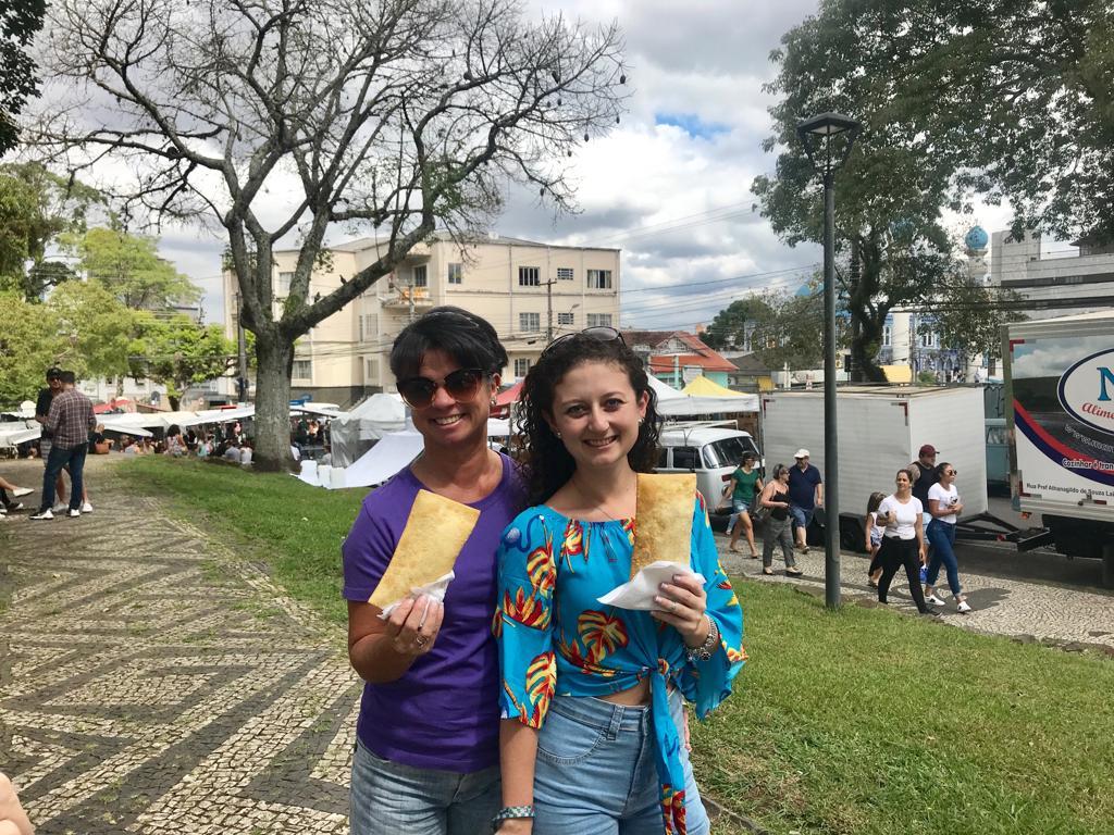 """As curitibanas Giovana Casagrande e Simone Gonçalves não negam o tradicional """"pastel de feira"""" no Largo da Ordem"""